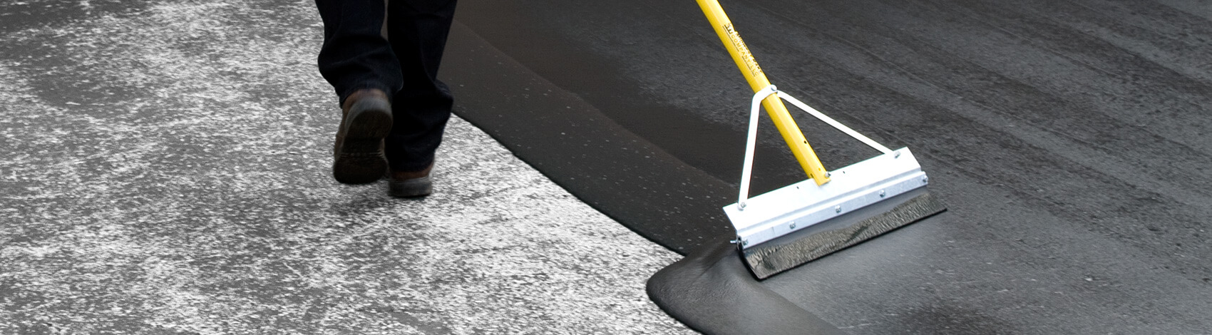 Asphalt sealer applied by squeegee to driveway